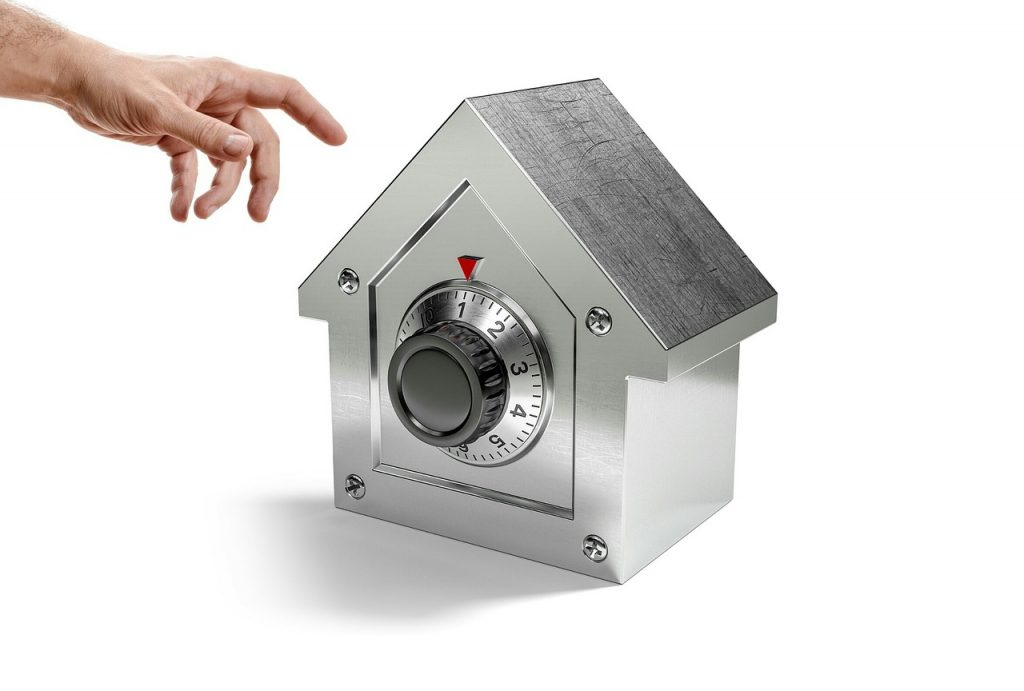 Hand approaching a house-shaped safe